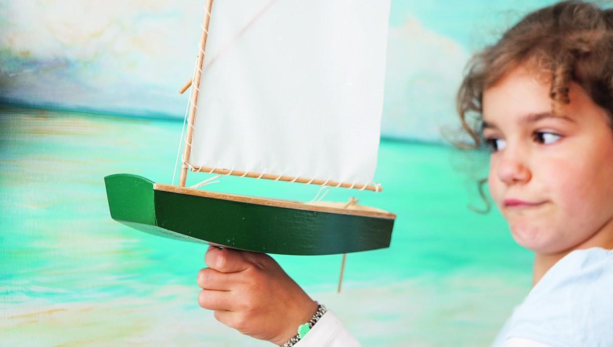 Ein Mädchen hält ein Segelschiff-Modell in der Hand