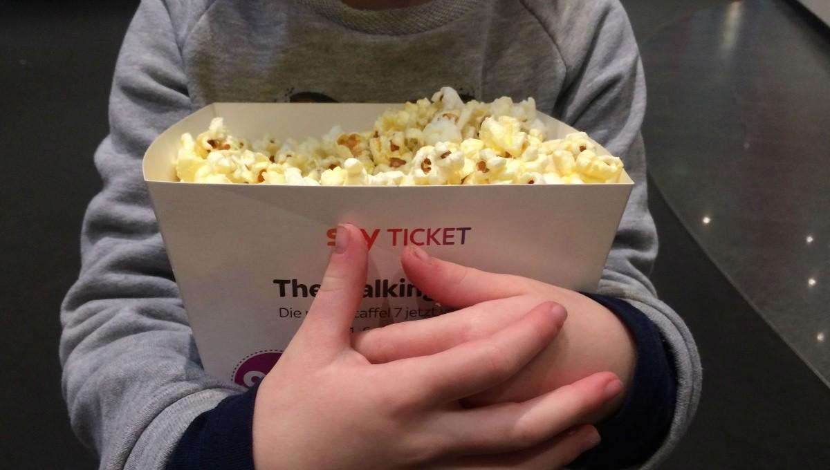 Kind mit Popcorn im Arm