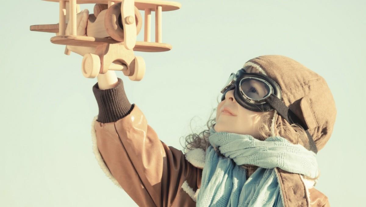 Junge mit Fliegerbrille hebt Spielzeugflugzeug in die Luft