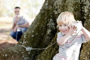 Vater und Sohn spielen Telefon im Garten