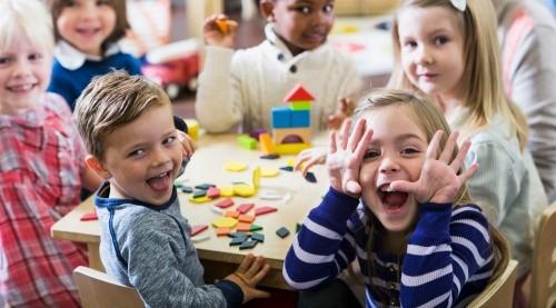 Fröhliche Kinder in der Kita mit Bauklötzen