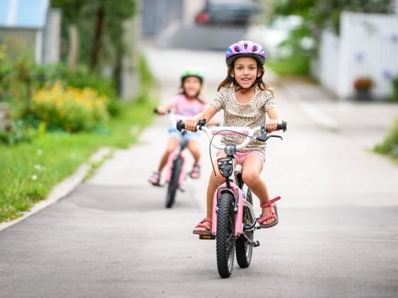 Mädchen fahren im Sommer Fahrrad