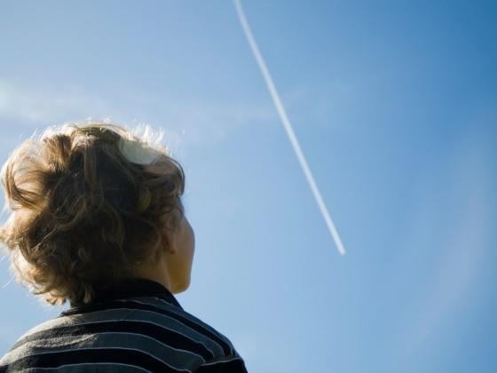 Junge schaut in den Himmel mit Kondensstreifen