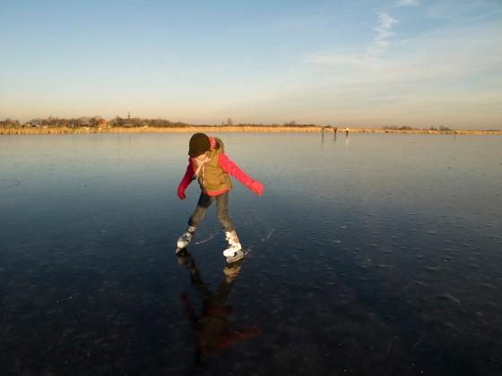 Kind fährt Schlittschuh auf See