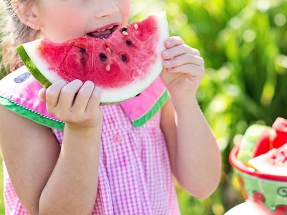 Mädchen beißt in Wassermelone