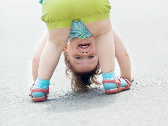 Kind beugt sich vor und guckt durch die eigenen Beine