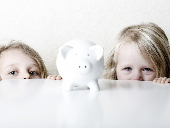 Zwei Mädchen gucken über Tischkante auf Sparschwein