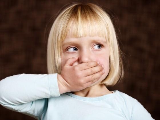 Mädchen hält sich die Hand vor den Mund