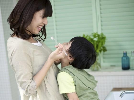 Die Mutter hilft dem Sohn beim Zähneputzen