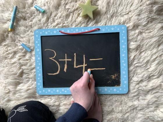 Kind rechnet an Tafel