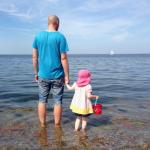Vater und Tochter blicken auf das Meer