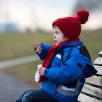 Ein Kind in Winterkleidung niest
