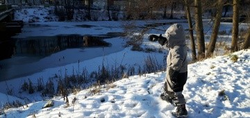 Kind an zugefrorenem See im Winter