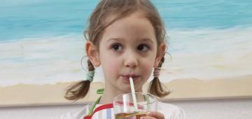 Kind trinkt Eistee aus dem Glas