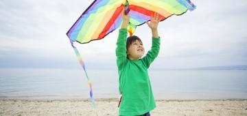 Junge beim Drachensteigen am Strand