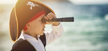 Als Pirat verkleideter Junge mit Fernrohr am Meer