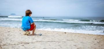 Junge sitzt auf Ball am Meer