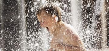 Junge unter Wasserfontäne