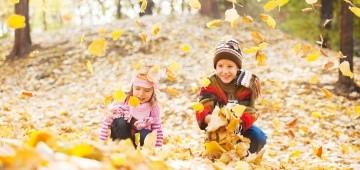 Zwei Kinder spielen mit Laub