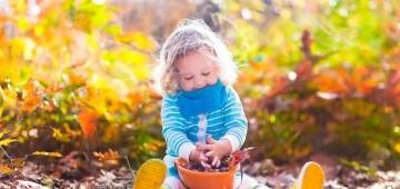Ein Mädchen spielt mit Eicheln in einem Eimer