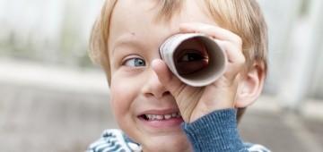 Ein Junge nutzt eine Klopapierrolle als Fernrohr