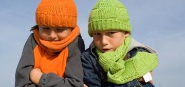 Zwei frierende Kinder mit bunten Mützen und Schals