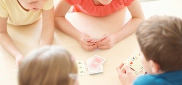 Kinder spielen Karten am Tisch