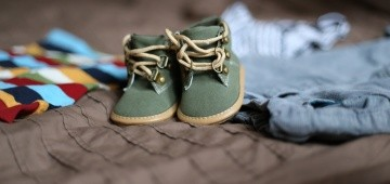Grüne Kinderschuhe auf anderer Kleidung