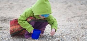 Kind sammelt Muscheln am Strand