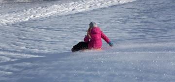 Ein Mädchen rodelt einen Berg hinunter
