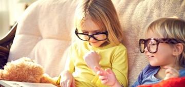 Zwei Kinder mit großen Brillen sitzen auf dem Sofa und lesen ein Lexikon
