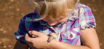 Mädchen mit Weinbergschnecke auf dem Arm