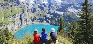 Drei Kinder sitzen oberhalb eines Bergsees