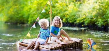 Kinder fahren mit einem Floß auf dem See