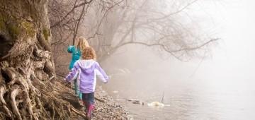 Zwei Mädchen laufen im Nebel am Fluss entlang