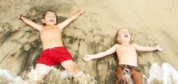 Zwei Kinder liegen am Strand im Spülsaum