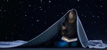 Kind liest unter der Bettdecke