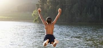 Ein Kind springt in einen See