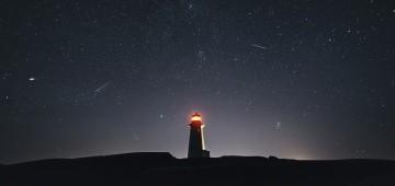 Nachthimmel mit Leuchtturm und Sternschnuppen