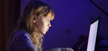 Mädchen sitzt im Dunklen vor einem erleuchteten Laptop