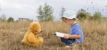 Ein Junge mit einem Buch und ein Teddybär sitzen sich gegenüber auf der Wiese