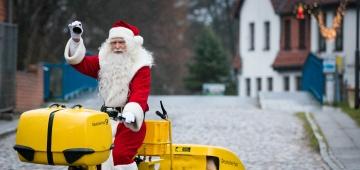 Weihnachtsmann auf einem Post-Fahrrad