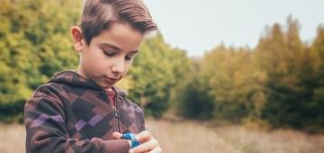Junge schaut auf seine Armbanduhr