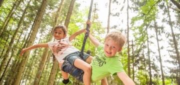 Zwei Jungs baumeln an einem Seil