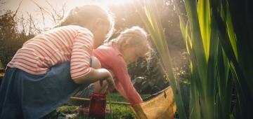 Zwei Mädchen keschern am Teich