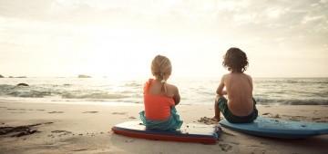 Zwei Kinder sitzen mit Bodyboards am Strand