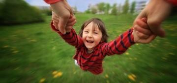 Ein Mädchen wird an den Armen seinen Eltern herumgewirbelt.